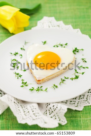 Fried egg on heart-shaped toast with cress and corn salad for Valentine's Day