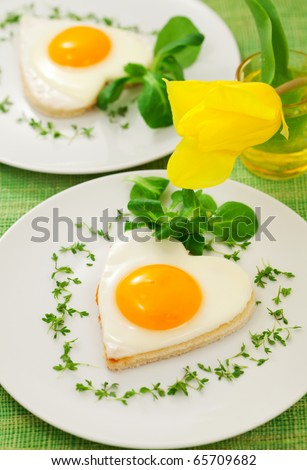 Fried egg on heart-shaped toast with cress and corn salad for Valentine's Day or Easter - stock photo