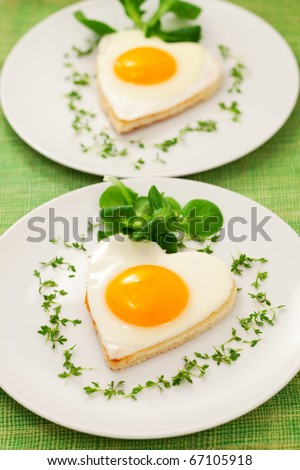 Fried egg on heart-shaped toast with cress and corn salad for Valentine's Day or Easter