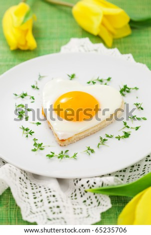 Fried egg on heart-shaped toast with cress and  for Valentine's Day or Easter
