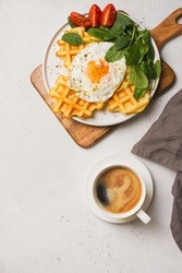 Fried egg, spinach, waffles and cup of coffee espresso on white background, flat lay, top view, copy space