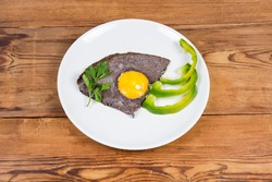 Fried egg sunny side up prepared by beating egg white mixed with black olives and unbroken yolk, slices vegetables on dish on old rustic table