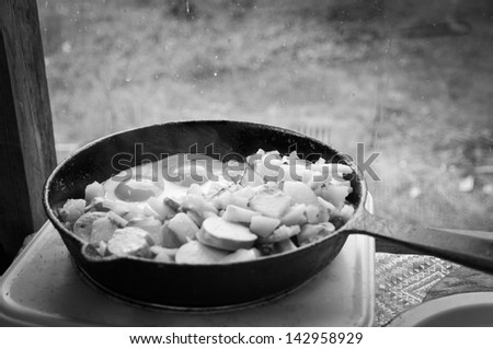 fried eggs and fried potatoes on a frying pan, a black-and-white photo