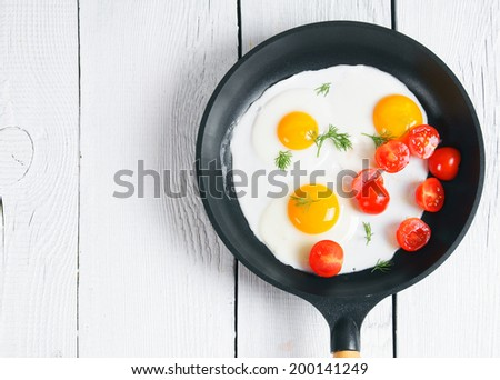 Fried eggs, fennel and fresh tomatoes in a frying pan. On a white, wooden background. #200141249
