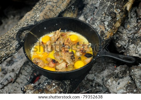 Fried eggs in a cast iron pan on campfire