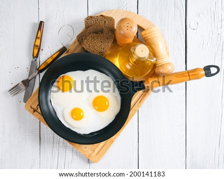 Fried eggs in a frying pan, an olive oil, rye bread, a saltcellar and tablewares on a chopping board. On a wooden background.