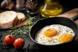 Fried eggs in a frying pan with cherry tomatoes and bread for breakfast on a black background.