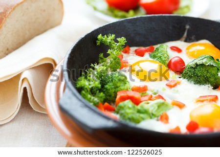 Fried eggs in a pan with vegetables, close-up