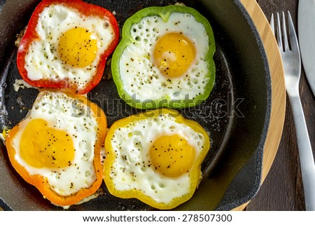 Fried eggs in green, yellow, red and orange bell peppers in cast iron skillet sitting on cutting board