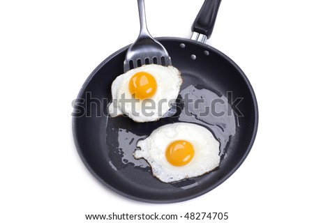 Fried eggs on a frying pan isolated on white background