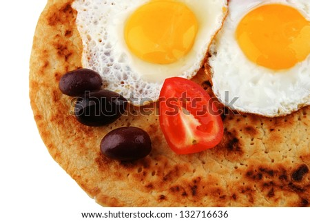 fried eggs on pancake over white background