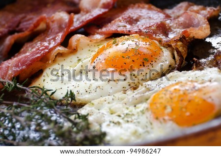 Fried eggs with bacon in a pan seasoned with herbs and pepper - stock photo
