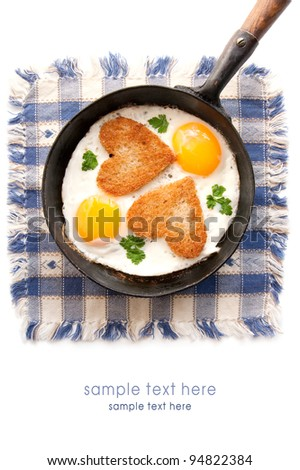 Fried eggs with slices of bread in the shape of a heart in the frying pan