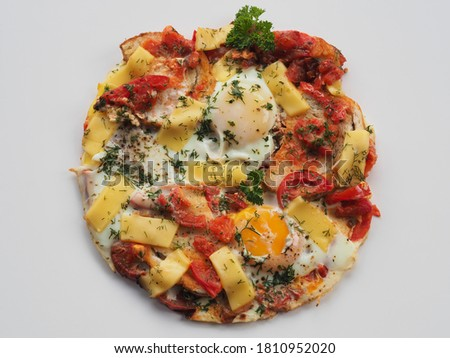 Fried eggs with tomatoes, cheese and herbs in a white plate closeup, top view. Traditional omlet dish with vegetables and chicken eggs Stok fotoğraf ©