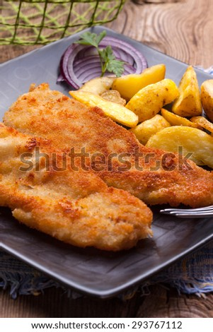 Fried fillet of cod with french fries on a dark plate. The selected focus point.