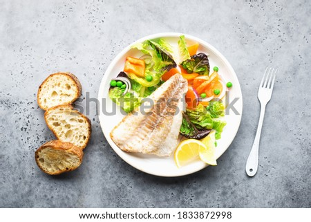 Fried fillet of sea white cod fish with juicy lettuce, capsicum, lemon, green peas on a large white dish on a gray background. Healthy balanced food. Top view ストックフォト ©