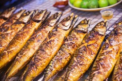 fried fish at a food market in Thailand. hot barbecue fish. spicy food on the counter of the night market. food Concept. a tourist spot with a spicy snack. sarpness on different objects.asian cuisine