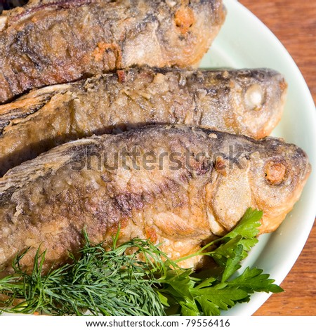 Fried fish carp in plate on wooden table