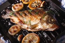 fried fish carp with lemon and onion on grill pan, horizontal close-up, rustic style