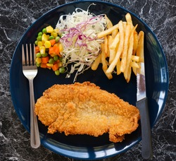 Fried Fish fillet and Fenfry and vegetable with spoon and Knive in blue plate