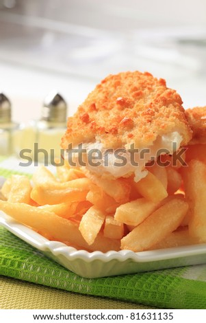 Fried fish fillet and heap of French fries