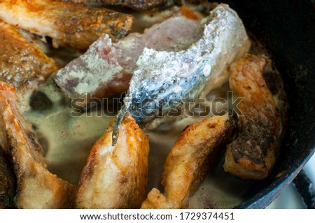 Fried fish snacks on frying pan. pieces of fried fish. pieces of fried fish in boiling oil. pieces of fried fish in hot oil in a frying pan