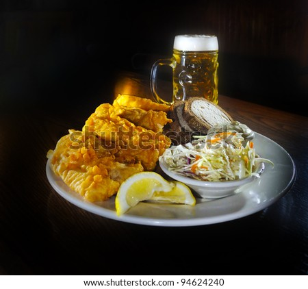 Fried Fish with coleslaw bread and tartar sauce, glass of beer in the back