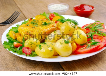 Fried fish with new potatoes, tomatoes, lettuce and herbs in the white plate