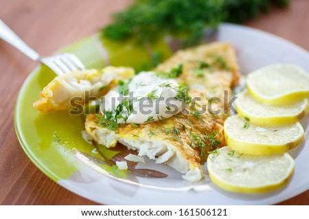 fried fish with sauce and lemon on a plate