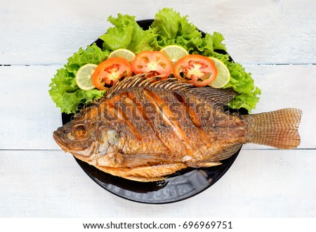 fried fish with vegetable on black dish. top view #696969751