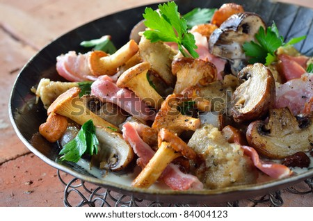 Fried fresh mushrooms, bacon and bread dumplings in a serving pan