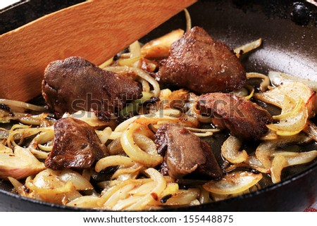 Fried goose liver with onion in a pan