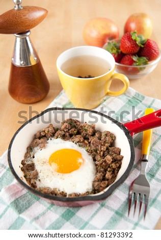 Fried Ground Beef with Fried Egg in Middle, Served with Strawberries and Tea
