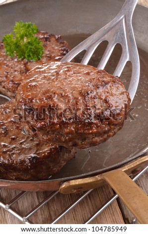 fried hamburger meat in a hot copper pan