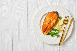 fried juicy salmon steak with lemon slices and parsley on a white plate on a wooden table, horizontal view from above, flat lay, free space