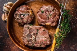 Fried lamb neck meat steaks in a wooden plate with herbs. Dark background. Top view.