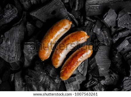 Fried meat sausages on a black background of charcoal. Cooked juicy hunting sausages on charcoal. Fried sausages on charcoal. Delicious fried sausages on coals, close-up photo. View from above