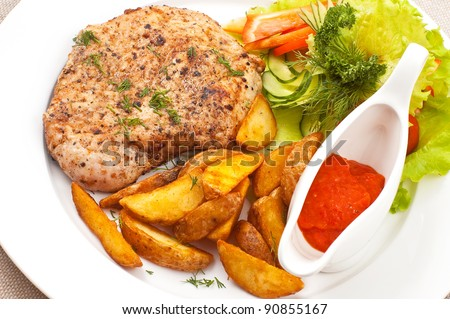 Fried meat with a potato, sauce and salad leaves on a white dish