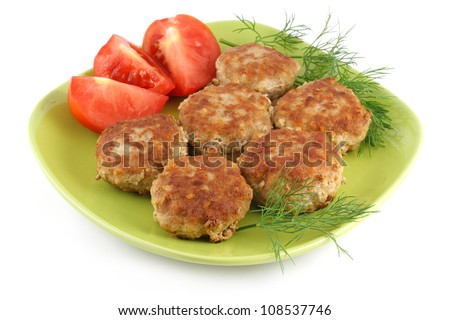 Fried meatballs and tomato on a green plate isolated on a white background