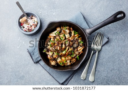Fried mushrooms with fresh herbs in black cast iron pan. Top view. #1031872177