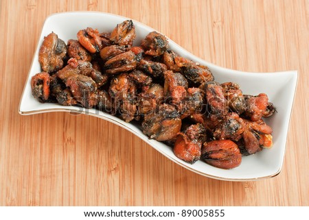 Fried mussels on the plate on a bamboo background