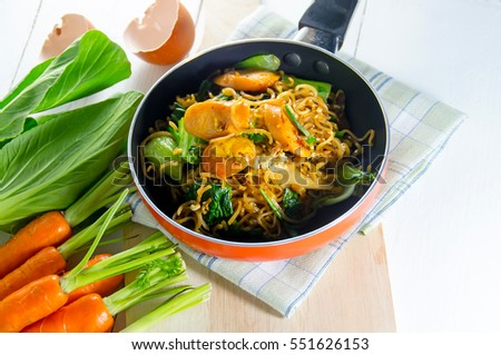 Stock Photo Fried noodle in pan on white table with fresh vegetables from the fram.