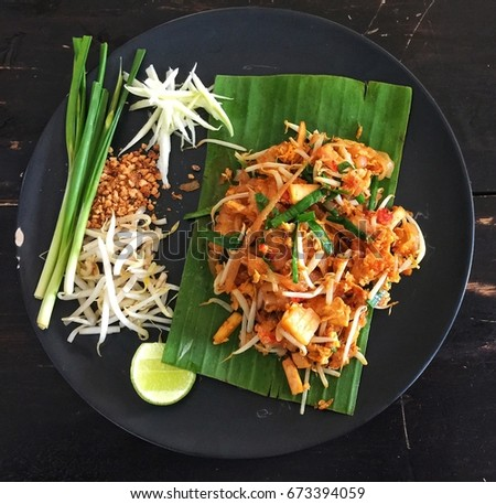 Fried noodle Thai style (pad thai) Delicious on a black plate on a wooden table that wants to be beautiful Causing hunger #673394059