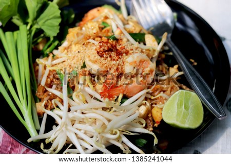 Fried noodle Thai style with prawns (Pad Thai in Thai language). This delicious menu is one of the Bangkok' popular street foods in Thailand. #1385241044