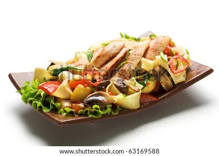 Fried Noodles with Fillet of Chicken and Vegetables. Garnished on Salad Leaf