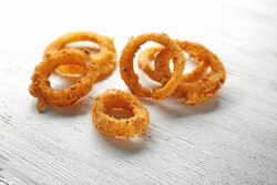 Fried onion rings on wooden background