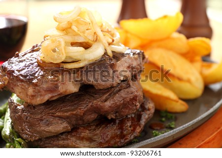 Fried onions on top of a stack of beef steaks.