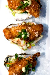Fried oysters or oysters Rockefeller. Classic fine dining restaurant appetizer. Deep fried oyster topped with fresh herbs and spices.