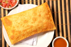 fried pastry on plate served with sauces on bamboo mat