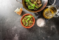 Fried peppers de padron or green pimientos in a pan and a traditional Spanish tapa bowl, salt, olive oil and bread on a dark gray background, copy space, high angle view from above, selected focus